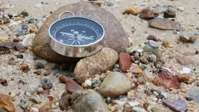 Tilt close up shot of the compass on the rock and sand beach with nature sea ambient sound.  stock video