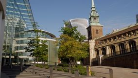 Tilt down the spire of the church of All Hallows. By The Tower with the skyline of The City of London behind. Taken on a sunny autumn morning stock footage