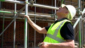 Male construction worker on building site inspecting and checking scaffolding for health and safety