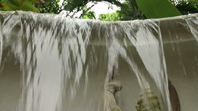 Tilt down from tropical trees to waterfall and mythical Garuda figure stock video footage