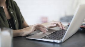 Tilt down of woman s hands typing and using touchpad. Close up of woman s hands typing at her laptop keyboard and using a touchpad in an office. Tilt down real stock video