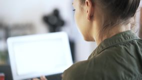 Tilt down of a woman typing at laptop in office. Tilt down of a young woman wearing a green shirt typing at her laptop in an office. Tilt down real time close up stock footage