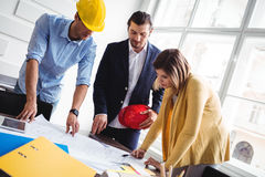 Tilt image of business people looking at blueprint Stock Photo