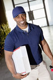 Tilt image of a happy African American delivery man looking at camera Royalty Free Stock Image