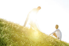 Tilt image of young couple spreading picnic blanket on grass during sunny day Royalty Free Stock Photos