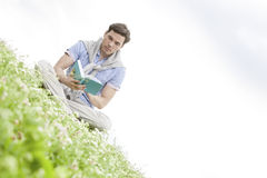 Tilt image of young man reading book while sitting on grass against sky Royalty Free Stock Image