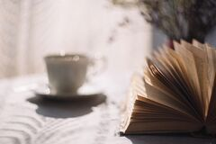 Tilt Lens Photography of Open Book With Ceramic Cup in Saucer Royalty Free Stock Photography