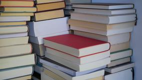 Tilt over a pile of stacked books stock video footage