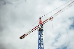 Tilt-shift defocused view of a crane. Against cloudy sky Royalty Free Stock Images