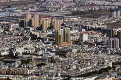 Tilt-shift effect on Chinese city in Yunnan. Densely built typical average size Chinese city. Buildings are tightly placed to each other whereas old compounds stock photography