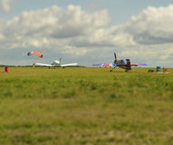 Tilt shift effect. Planes and parachutist on airfield Stock Image