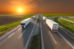 Tilt shift image of delivery trucks on the highway. Many white trucks driving towards the sun. Fast blurred motion driving on the freeway in tilt shift technique stock photo