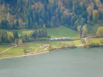 Tilt shift image of train in autumn landscape next to lake royalty free stock photography