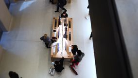 Tilt-shift lens over people shopping inside Apple Store. Paris, France - Circa 2019: Tilt-shift lens over people shopping for new iMac Pro, iPhone 11 Pro iPad stock video