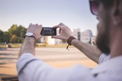 Tilt Shift Photo of Man Holding Black Smartphone Taking Photo of Gray Ground at Daytime Royalty Free Stock Image