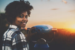 Tilt-shift shooting black girl near binocular. Cute biracial teenage female in plaid shirt is using street telescope to observe evening cityscape, young black stock images