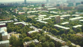 Tilt shift time lapse shooting of street from high above. Of multiple roofs and residential buildings with green trees, road and city traffic, strongly blurred stock footage
