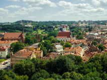 Tilt and shift view of Latvia houses and their sunny roofs among green trees Royalty Free Stock Photography