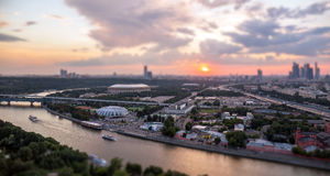 Tilt and shift view of sunset panorama of Moscow with pink clouds, traveling boats and river reflections Royalty Free Stock Images