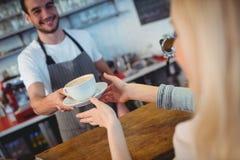 Tilt shot of barista serving coffee to woman at cafe. Tilt shot of young male barista serving coffee to woman at cafe Royalty Free Stock Image
