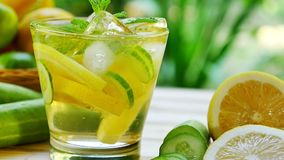 Tilt shot for glass of detox water drink with lemon and cucumber stock footage