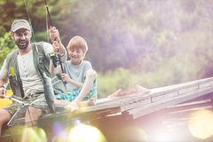 Tilt shot of happy father and son catching fish royalty free stock photography