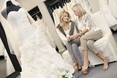 Tilt shot of mother and daughter sitting with footwear in bridal store Royalty Free Stock Photo