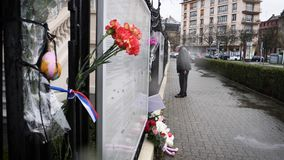 Tilt to flowers, toys at entrance of Russian Consulate Embassy mourning. STRASBOURG, FRANCE - MAR 28, 2018: Carnation flower with Russian Flag band at Russian stock video footage