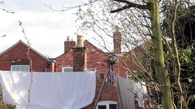 Tilt to Washing Line - Socks, Sheets, Clothes & Towels Hanging in Victorian House Garden - Town / City Life. stock video footage