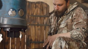 Tilt up of bearded young man blacksmith using hydraulic press for steel arms manufacture at smithy workshop stock video