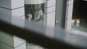 Tilt up of businesswoman and businessman colleagues talking in moving elevator and come out from it in modern business. Center indoors stock video