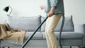 Tilt-up of happy guy in headphones dancing vacuuming carpet at home