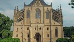 Tilt up panorama of frontal facade of St Barbara Church in Kutna Hora in spring sunny day. Moving from grass to building stock video footage