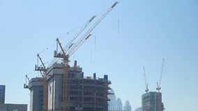 Tilt up panorama of huge construction cranes are in unfinished building in big modern city. Against clear blue sky in summer day stock video footage