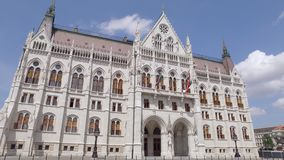 Tilt up panorama view from ground to Hungarian Parliament Building in sunny day, neo-gothic. And beaux-arts architectural styles stock video