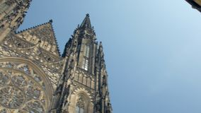 Tilt up panoramic view from ancient gothic church St Vitus cathedral to blue sky in Prague. In sunny day stock video footage