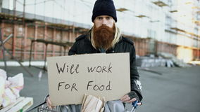 Tilt up of portrait of young homeless man with cardboard looking at camera and wants to work for food standing near stock footage
