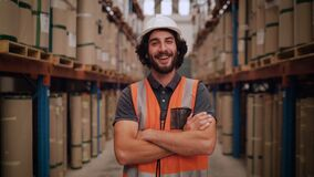 Tilt up short of a young male warehouse worker or a supervisor in a warehouse smiling and looking at camera
