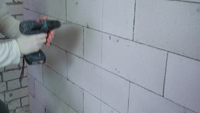 Tilt up shot of builder drilling holes in block wall with electric drill. Tilt up shot of builder drilling holes in aerated concrete block wall with electric stock video footage