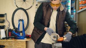 Tilt-up shot of mechanic working with electric circular saw fixing small metal part. Shielding spectacles and protective. Tilt-up shot of busy mechanic working stock video footage