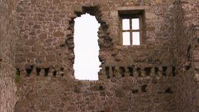 A long castle window. A tilt up shot of a castle`s window. The castle is ruined and old stock video footage