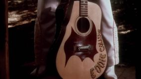Tilt up shot of  Elvis impersonator with guitar stock video footage