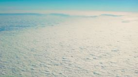 Tilt up shot of a green airplane engine flying over clouds.  stock footage