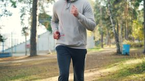 Tilt-up shot of handsome guy in trainers and tracksuit jogging in park wearing headphones and enjoying physical activity. And autumn nature. People, technology stock footage
