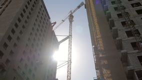 Tilt up shot of huge construction crane between two unfinished buildings. Against sun in daytime stock video footage