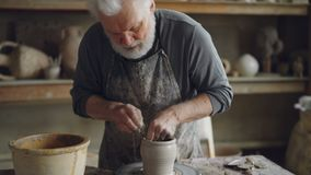 Tilt-up shot of skilled craftsman professional potter molding clay and making pot on throwing wheel. Grey haired bearded stock video footage