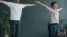 Tilt-up slow motion of man and woman young couple doing yoga in cozy studio stock video footage