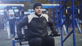 Tilt up of Young athlete man doing exercise at outdoor gym in winter park Royalty Free Stock Images