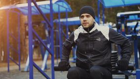 Tilt up of Young athlete man doing exercise at outdoor gym in winter park Royalty Free Stock Image
