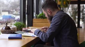 Tilt up of young man and young woman study together in cafe. Guy and girl study together in a cafe stock video